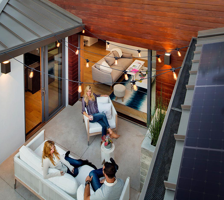 People sitting outside home with solar panels on roof
